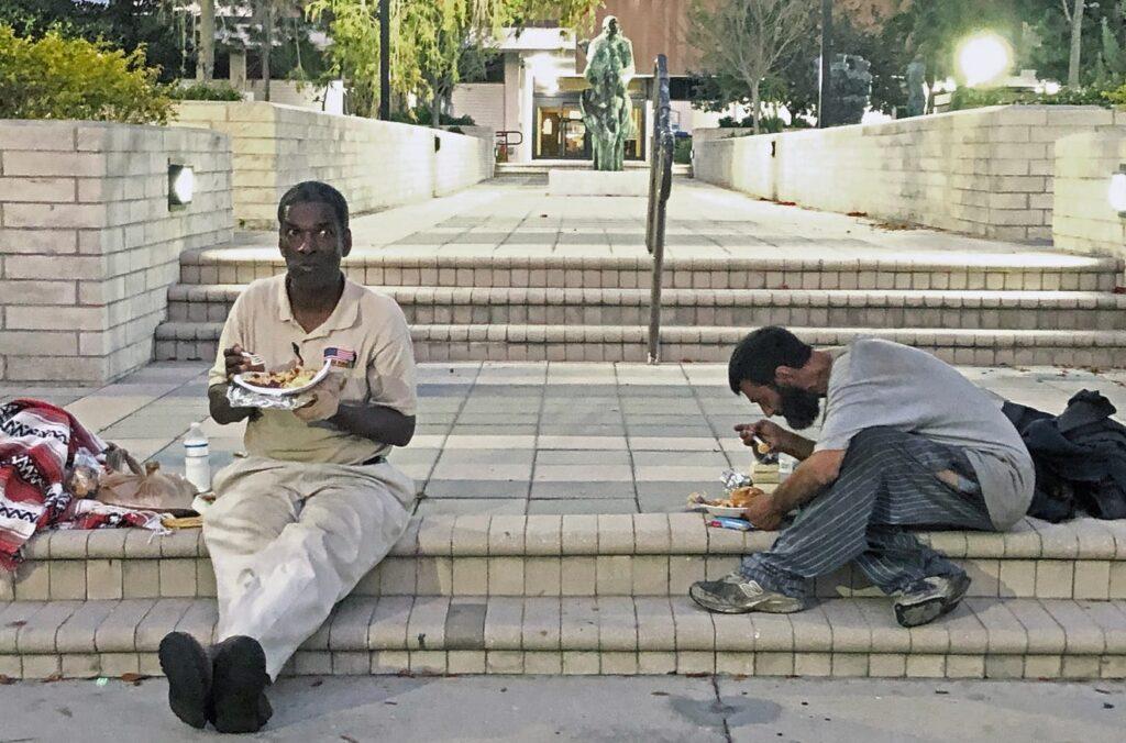 two homeless men sitting on sarasota court steps