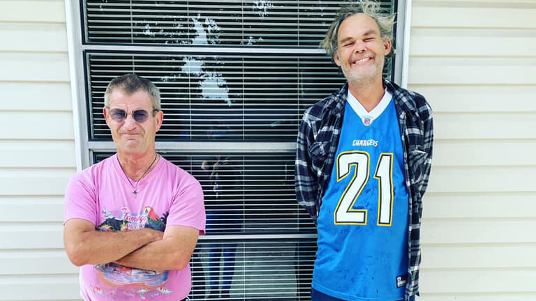 Two homeless mentally ill men standing in front of their nonprofit Second Heart Homes house
